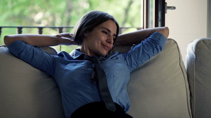 Young, pretty businesswoman relaxing on sofa at home