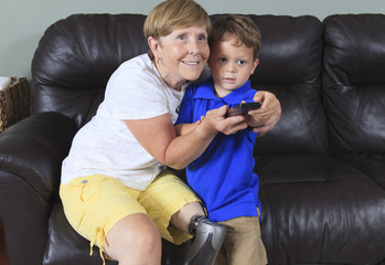 Woman with a prosthetic leg and her grandson and remote control