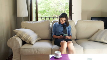 businesswoman using smartphone sitting on sofa at home