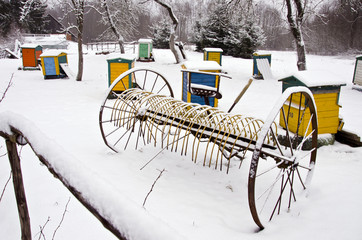 snowy horse drawn hay rake and beehive in winter farm garden