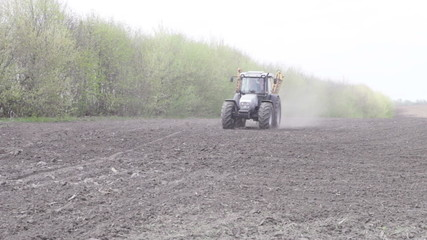 tractor with sprayer turns on the black field on a background