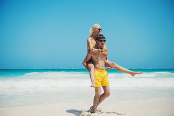 Man giving piggyback ride to girlfriend at the beach. Holiday
