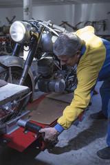 man adjusting a motorbike.