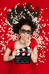 Puzzled Girl with 3D Cinema Glasses,  Popcorn and Clapboard