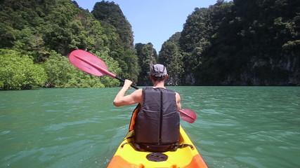 elderly man rowing a kayak across the azure sky-blue sea