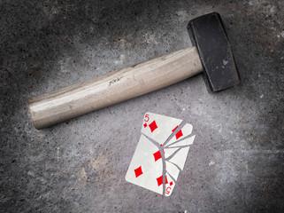 Hammer with a broken card, five of diamonds