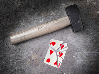 Hammer with a broken card, six of hearts