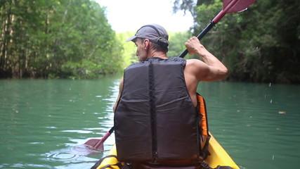 elderly man kayak rowing kayak on the river and talking