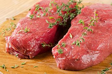 Raw  steak on  a  cutting board.