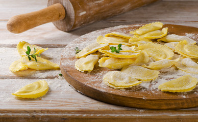 Fresh Ravioli on with flour  on a  wooden backround.