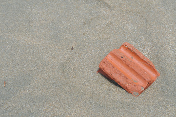 Bit of red brick half buried in sea sand