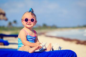 cute little baby girl with seashells on tropical beach