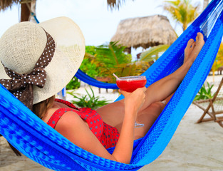 woman with cocktail relaxed on tropical beach