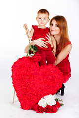 Happy mother and her daughter with big red heart