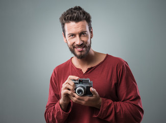 Young man taking pictures with a vintage camera