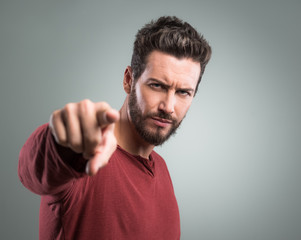 Angry young man pointing at camera
