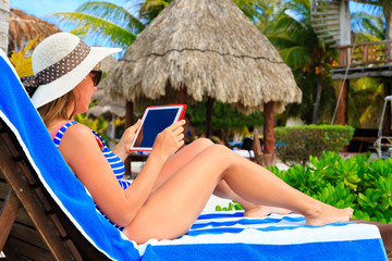woman with touch pad on tropical vacation