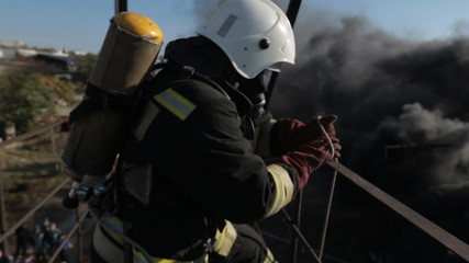 Firefighters wearing gas masks do their work in smoke at a high