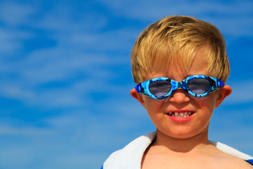 happy boy in swimming goggles on sea vacation