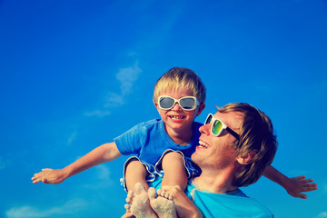 Father and son playing on blue summer sky