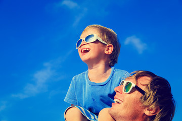 Father and son having fun on summer sky