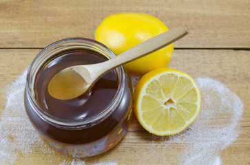 Jar of dark honey a wooden spoon and lemons