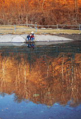 Children play on the banks of a pond of water