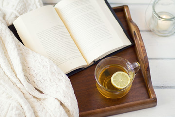 Comfortable homey scene: Book on a tray with a candle