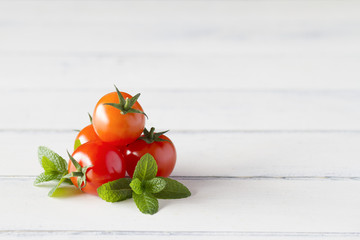 Red tomatoes and peppermint on white wooden table