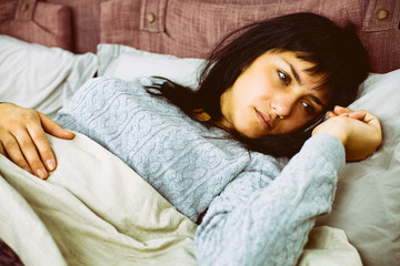 Portrait of sad woman lying in bed after breaking up