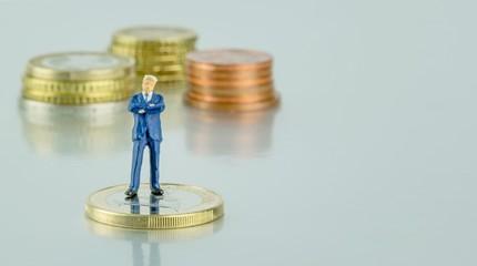 A successful miniature businessman standing on money