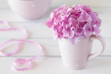 Hydrangea in a cup and a pink checkered ribbon. Vintage