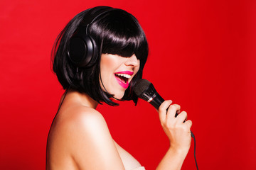 Woman with microphone singing on headphones and enjoying a dance