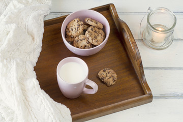 Homey scene: cookies, a cup with milk on a tray and a candle