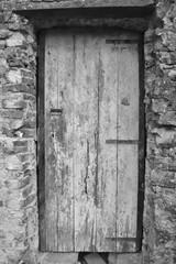 Italian Wooden Door in Stone Wall in Monochrome