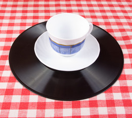 Clean cup and plate on vinyl disc and red vichy tablecloth