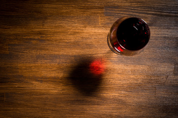 Glass of red wine on wooden table. Top view