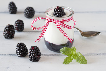 Greek yogurt and blackberry jam on a white wooden table