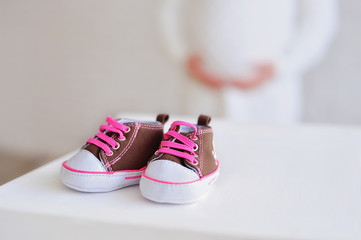 Newborn baby girl booties and pregrant belly
