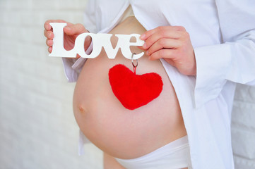 Pregnant woman belly closeup with love sign and a heart