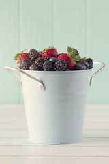 Bucket full of berries. Robin egg blue background