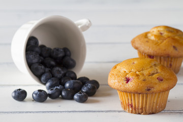 Blueberry muffins. A cup with blueberries. White wooden table.