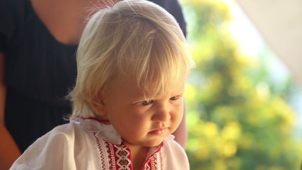small blonde baby girl in embroidery dress watching cartoon