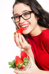 Happy woman eating strawberries