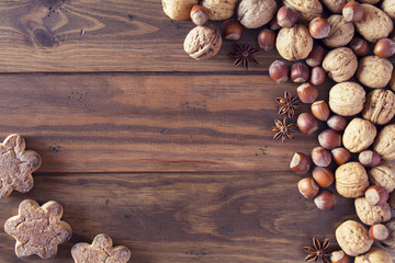 Walnuts, star anise and hazelnuts in shells on a board