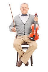 Senior sitting on a chair and holding a violin