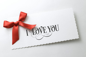 I love you text on white letter with red ribbon