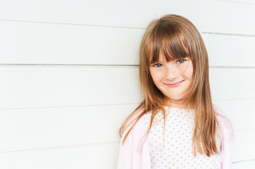 Portrait of adorable little girl against white wooden background