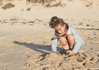 Little girl playing in the sand of the beach