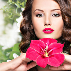 beautiful adult girl with bright red lips and flower near the fa